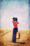 Redhead girl with suitcase at countryside road. Near wheat field. Photo in old color image style Royalty Free Stock Image