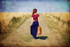 Redhead girl with suitcase at countryside road. Near wheat field. Photo in old color image style stock photography