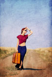 Redhead girl with suitcase at countryside road Royalty Free Stock Images