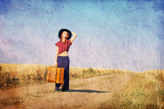 Redhead girl with suitcase at countryside road Stock Photos