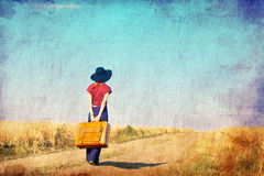 Redhead girl with suitcase at countryside road. Near wheat field. Photo in old color image style Royalty Free Stock Photos