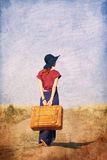 Redhead girl with suitcase at countryside road. Near wheat field. Photo in old color image style Stock Photo