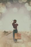 Redhead girl with suitcase at countryside road Stock Images