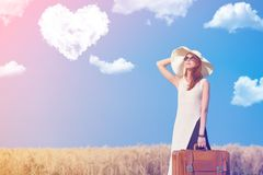 Redhead girl with suitcase at countryside road. Near wheat field with heart shape clouds at background Stock Photos