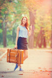 Redhead girl with suitcase Stock Images