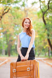 Redhead girl with suitcase Stock Photography