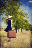 Redhead girl with suitcase at tree's alley. Royalty Free Stock Photos