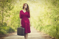 Redhead girl with suitcase. At tree's alley. Photo in old retro style Royalty Free Stock Photography