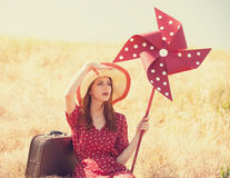 Redhead girl with suitcase. And wind turbine sitting at grass Stock Photos