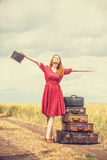 Redhead girl with suitcases Royalty Free Stock Photos