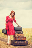 Redhead girl with suitcases Royalty Free Stock Image