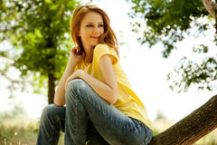 Redhead girl at summer park. Royalty Free Stock Image