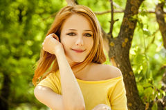 Redhead girl at summer park. Royalty Free Stock Images