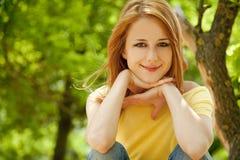 Redhead girl at summer park. Stock Photo