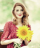 Redhead girl with sunflower at outdoor. Royalty Free Stock Image