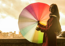 Redhead girl on sunset. Beautiful young and smiling red head girl twisting and spinning a rainbow colored umbrella during a sunset in front of the Italian city Stock Photography