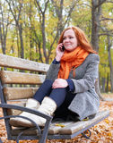 Redhead girl talk on phone and sitting on a bench in city park, fall season Royalty Free Stock Photo