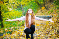 Redhead girl throwing leaves in autumn park Royalty Free Stock Images