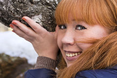 Redhead girl touches the bark of a birch. Stock Image