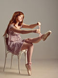 Redhead girl trying on pointe shoes Royalty Free Stock Photos