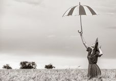 Redhead girl with umbrella at wheat field stock photo