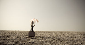 Redhead girl with umbrella at windy field. Stock Photos