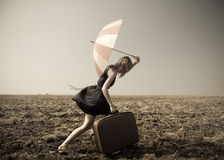 Redhead girl with umbrella at windy field. Photo in old image style Stock Photography