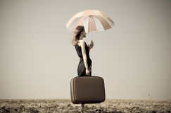 Redhead girl with umbrella at windy field. Stock Images