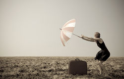 Redhead girl with umbrella at windy field. Royalty Free Stock Image