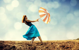 Redhead girl with umbrella at windy field. Royalty Free Stock Images