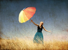 Redhead girl with umbrella at windy grass meadow. Photo in old color image style Royalty Free Stock Image
