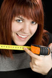 Redhead girl using measuring tape tool Stock Photo