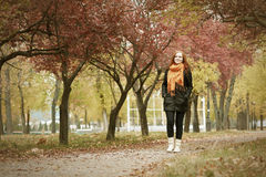 Redhead girl walk on pathway in city park, fall season Royalty Free Stock Image