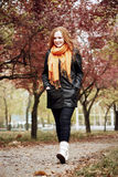 Redhead girl walk on pathway in city park, fall season Royalty Free Stock Photo