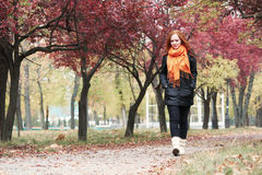 Redhead girl walk on pathway in city park, fall season Royalty Free Stock Photography