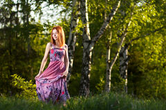 Redhead girl walking under rays of sunset forest Royalty Free Stock Image