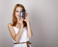 Redhead girl in white dress with vintage camera. Royalty Free Stock Photo
