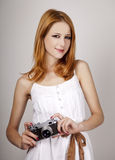 Redhead girl in white dress with vintage camera. Royalty Free Stock Photography