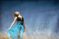 Redhead girl at windy field. Photo in old color image style Royalty Free Stock Images