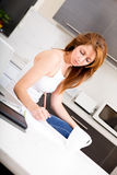 Redhead girl working in kitchen Royalty Free Stock Image