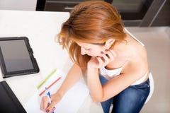 Redhead girl writing in kitchen Stock Photo
