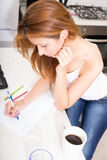 Redhead girl writing in kitchen Stock Images