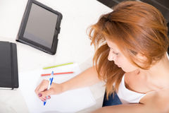 Redhead girl writing in kitchen Royalty Free Stock Images