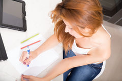 Redhead girl writing in kitchen Royalty Free Stock Photo