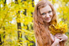 Redhead girl with yellow autumn leaves Royalty Free Stock Photos