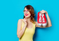 Girl holding gumshoes. Redhead girl in yellow dress and colored glasses holding gumshoes on blue background Royalty Free Stock Image