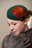 Redhead in green feathered hat and fur Stock Image