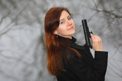 Redhead with a gun. Young woman with long red hair holding a gun in her hands Stock Image
