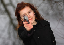 Redhead with a gun. Young woman with long red hair holding a gun in her hands aiming right at the camera Stock Photo