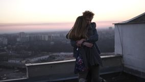 Redhead guy whirls his girlfriend on the roof with a cityscape and sunset horizon on the background. Happy time together. Dating in romantic places stock video footage